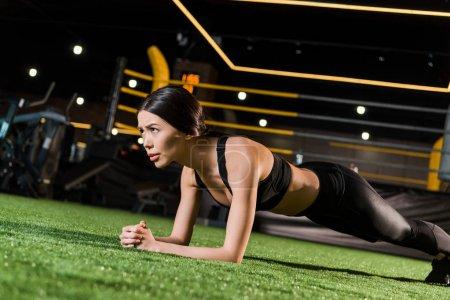 Photo pour Vue de bas angle de femme attrayante faisant l'exercice de planche sur l'herbe - image libre de droit