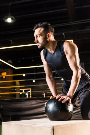low angle view of serious man standing near squat box while holding ball