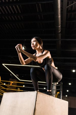 low angle view of attractive woman doing squat exercise on squat box