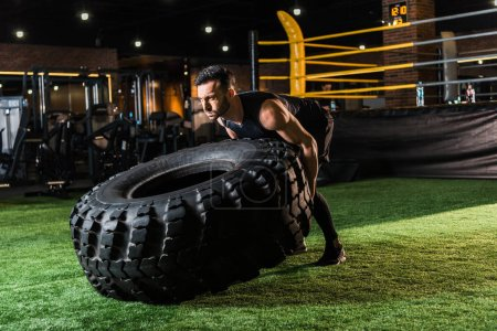 Photo for Strong athletic man working out with huge car tire on green grass - Royalty Free Image