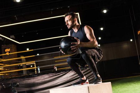 low angle view of serious sportsman doing squat on squat box while holding ball