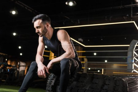 Photo for Low angle view of athletic man sitting on car tire in gym - Royalty Free Image