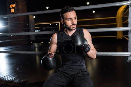 Photo pour Bel homme barbu dans des gants de boxe noirs dans la salle de gym - image libre de droit