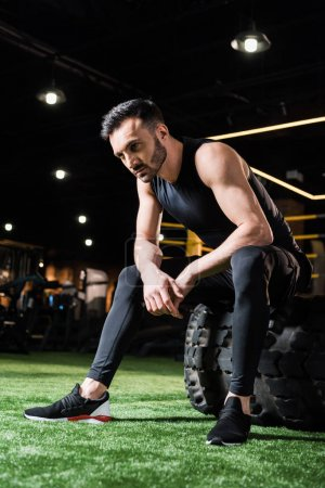 low angle view of handsome and tired athletic man sitting on car tire in gym