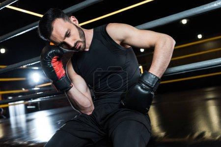 Photo pour Vue d'angle bas de l'homme barbu fatigué dans les gants noirs de boxe touchant la tête dans la gymnastique - image libre de droit