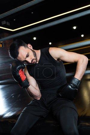Photo pour Vue d'angle bas de l'homme barbu épuisé dans les gants noirs de boxe touchant la tête dans la gymnastique - image libre de droit