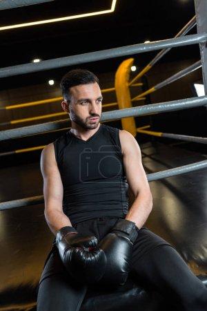 Photo pour Homme barbu fatigué dans les gants noirs de boxe s'asseyant dans la gymnastique - image libre de droit