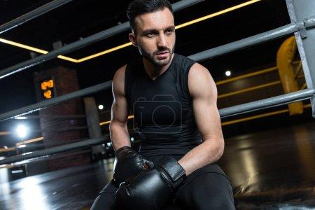 Photo pour Vue d'angle bas de l'homme confiant dans des gants de boxe s'asseyant dans la gymnastique - image libre de droit