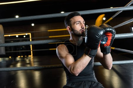 Photo for Athletic man in boxing gloves drinking water in sports center - Royalty Free Image