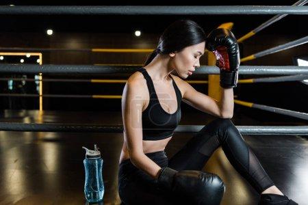 Photo pour Attrayant femme en gants de boxe toucher la tête près de bouteille de sport dans la salle de gym - image libre de droit