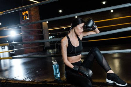 Photo for Tired woman in boxing gloves touching head near sport bottle in gym - Royalty Free Image