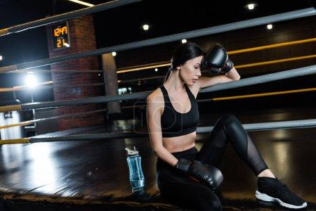 Photo pour Femme fatiguée dans des gants de boxe touchant la tête près de la bouteille de sport dans la gymnastique - image libre de droit