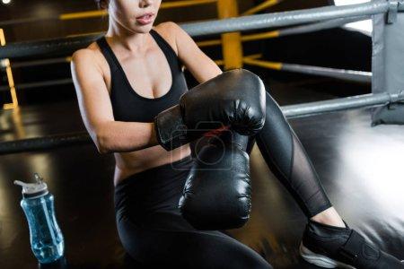 Photo pour Vue recadrée de femme dans des gants de boxe s'asseyant près de la bouteille de sport - image libre de droit