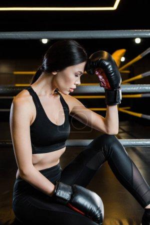 Photo pour Femme fatiguée dans des gants de boxe touchant la tête dans la gymnastique - image libre de droit