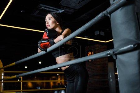 Photo pour Vue d'angle bas de la femme attirante dans des gants de boxe restant dans le centre sportif - image libre de droit