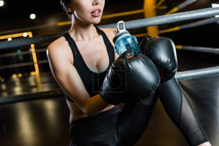 Photo for Cropped view of athletic woman in boxing gloves holding sport bottle - Royalty Free Image