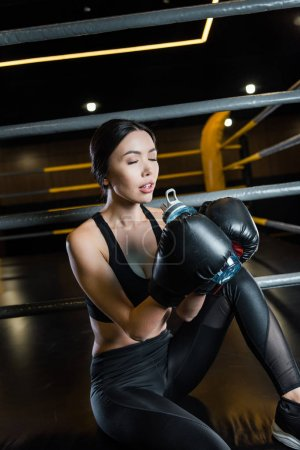 Photo pour Jolie femme avec les yeux fermés tenant bouteille de sport tout en portant des gants de boxe - image libre de droit