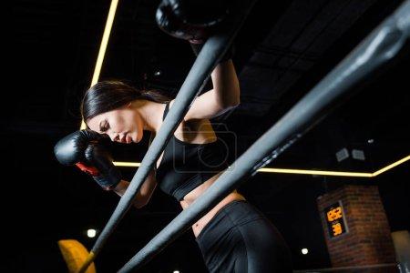 Photo pour Vue d'angle bas de belle femme dans des gants de boxe restant dans la gymnastique - image libre de droit