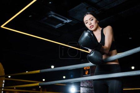 Photo pour Vue à angle bas de femme contrariée regardant des gants de boxe tout en se tenant dans la salle de gym - image libre de droit
