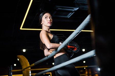 vista de ángulo bajo de la mujer en guantes de boxeo de pie en el gimnasio