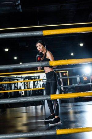 Foto de Selective focus of attractive woman boxing while standing in boxing gloves in gym - Imagen libre de derechos