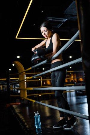 Photo pour Vue à angle bas de la femme sportive regardant des gants de boxe tout en se tenant près de la bouteille de sport - image libre de droit
