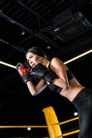 Foto de Low angle view of confident young woman boxing while standing in boxing gloves in gym - Imagen libre de derechos
