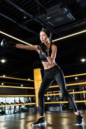 Photo pour Vue à angle bas de la boxe jeune femme tout en restant dans des gants de boxe dans la salle de gym - image libre de droit