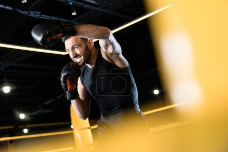 Photo for Low angle view of bearded and strong man boxing in gym - Royalty Free Image