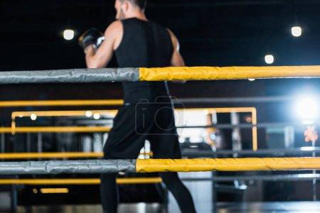 Photo pour Foyer sélectif de l'anneau de boxe avec des cordes près de l'homme athlétique exercice dans les gants de boxe - image libre de droit