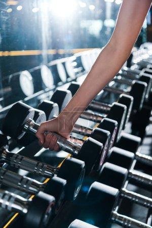 Photo pour Vue recadrée de la sportive prenant haltère dans la salle de gym - image libre de droit