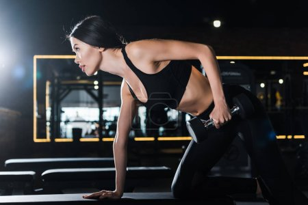 Photo for Attractive athletic woman working out with dumbbell in gym - Royalty Free Image