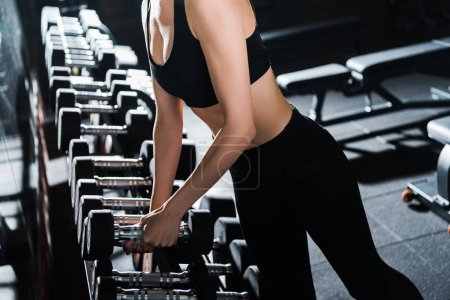Photo for Cropped view of athletic young woman taking dumbbells in gym - Royalty Free Image
