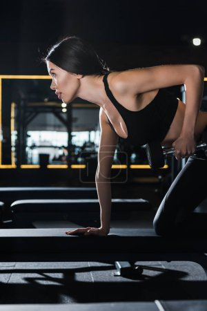 pretty and athletic woman working out with dumbbell in gym