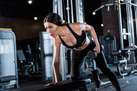 Photo for Low angle view of strong and athletic woman working out with dumbbell in gym - Royalty Free Image