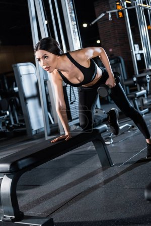 Photo pour Vue bas d'angle de belle jeune femme travaillant dehors avec l'haltère dans la gymnastique - image libre de droit