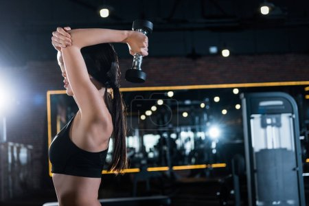 young athletic woman working out with dumbbell in gym