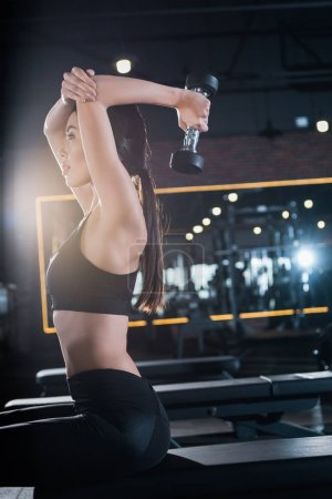 Photo for Attractive young and athletic woman working out with dumbbell in gym - Royalty Free Image