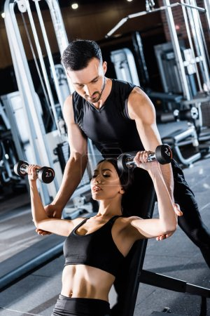 Photo for Selective focus of young athletic woman working out with dumbbells near handsome  trainer in gym - Royalty Free Image