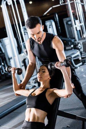 Photo pour Foyer sélectif de la jeune femme athlétique travaillant avec haltères près de beau entraîneur dans la salle de gym - image libre de droit