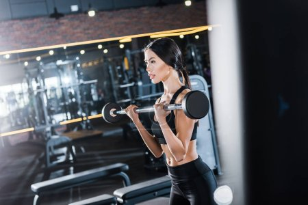 Photo for Selective focus of attractive woman working out with barbell in gym - Royalty Free Image
