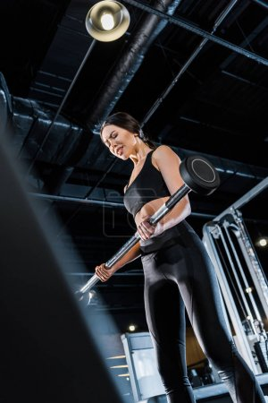 Photo for Low angle view of strong young woman exercising with heavy barbell in gym - Royalty Free Image