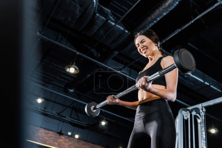 Photo for Low angle view of young woman with closed eyes exercising with heavy barbell in gym - Royalty Free Image