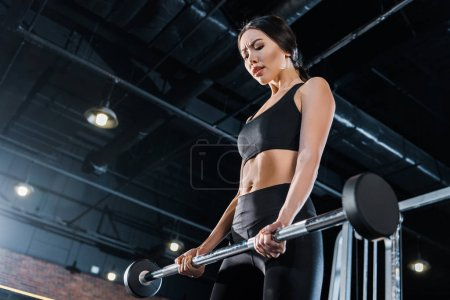 Photo for Low angle view of attractive young woman exercising with heavy barbell in gym - Royalty Free Image