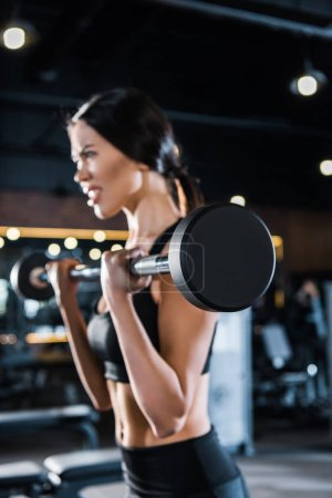 Photo for Selective focus of strong young woman exercising with heavy barbell in gym - Royalty Free Image