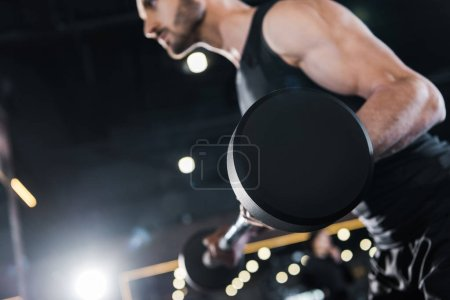 Photo for Selective focus of strong man exercising with heavy barbell in gym - Royalty Free Image
