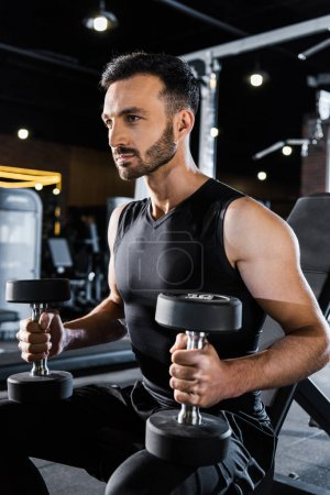 Photo for Handsome athletic man working out with dumbbells in gym - Royalty Free Image