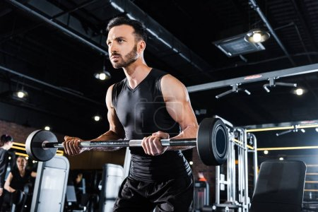 Photo for Low angle view of athletic man exercising with heavy barbell in gym - Royalty Free Image