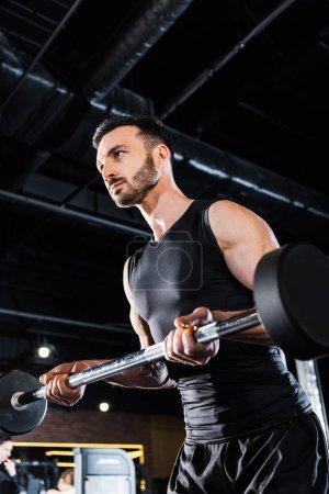 Photo pour Vue d'angle bas de l'homme athlétique travaillant dehors avec le barbell lourd dans la gymnastique - image libre de droit