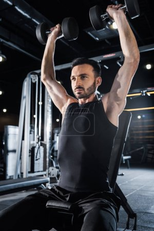 Photo for Low angle view of handsome athletic man working out with dumbbells in gym - Royalty Free Image